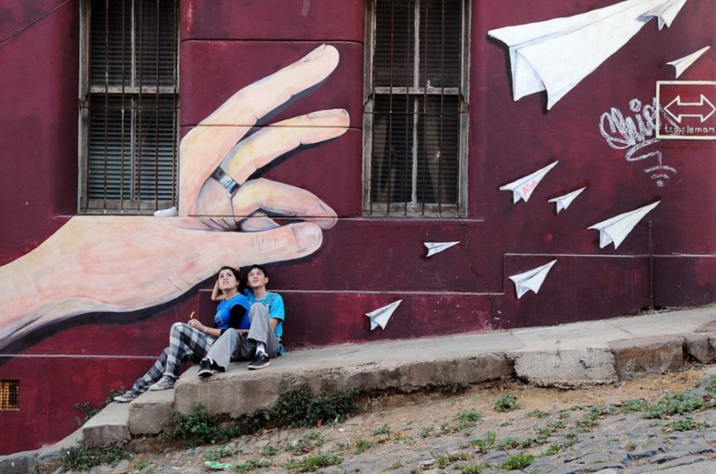 Valparaiso, Chile: children sitting in front of a mural looking at an airplane flying overhead